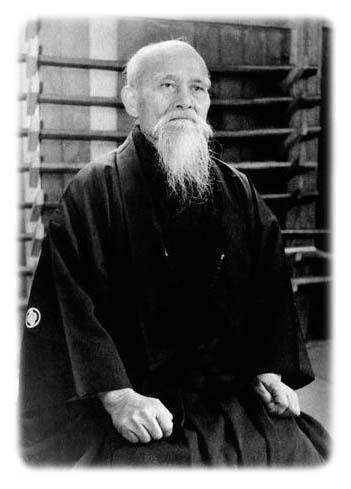 O Sensei in seinem Dojo vor einem Waffenständer