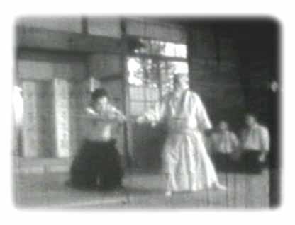 O Sensei demonstriert Ki - während er den Jo hält vermag es sein Schüler nicht diesen wegzudrücken, er ist wie versteinert